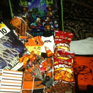 Here's the whole loot pile, including the disney haunted house bag, the spiderweb w/ ghost, Halloween socks, kitchen towels, stickers, candy and chees