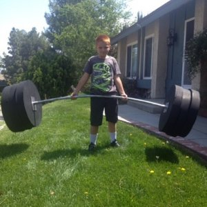 "My nephew holding the 500 lb weight set for the ""Worlds Strongest"" display. (Made from PVC and foam)"