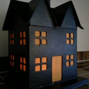 Easy haunted house - Paper mache house from Hobby Lobby spray-painted black with orange vellum taped over windows.   Place led flicker candle inside.