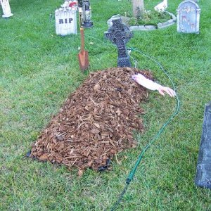 The newly-filled grave. (The hand slowly moves up and down)