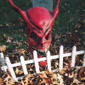 Red Demon mask covering a solar powered security light.  Both the light and the white mini-picket fencing were used to frame the graveyard.  I placed