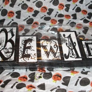009 I love this wrapping paper.  and the black ribbon that tied this gift is nice too.  I will use the ribbon in a craft.  the beware sign is sitting