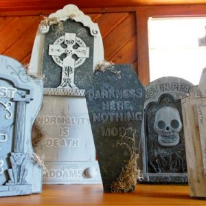 Dollar store tombstones altered with foam letters, cardboard, and acrylic paints.