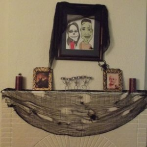 Our mantle. The large picture is normally a caricature of my boyfriend and I. I traced, colored, and spookified it for halloween
