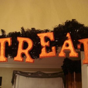 This is a garland I made. The whole phrase says Trick or Treat. I painted and glittered the letters and attached them to a black garland.