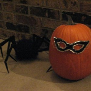 a creepy spider lurks behind a masked pumpkin