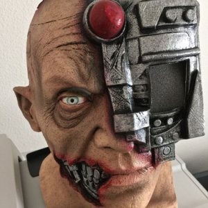 BUYCOSTUMES, 2015. Cyborg full head latex mask with digital eye. Your iPhone slides in the top of the eye area from the outside and you play a digital