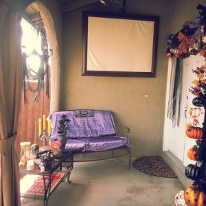 Candy distribution area...with ghost projection on picture frame...hand crafted pumpkin garland...haunted mansion wallpaper bench