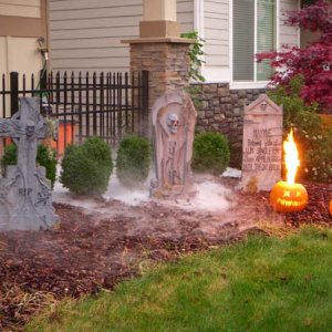 Small burial plot.  Tombstones cast in A/B foam (from Tap Plastics), the fog chiller is running, and my propane pumpkin is fired up.