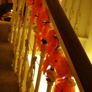 I hand made 80 marigolds out of layered tissue paper and pipecleaners, then wound them all around the staircase. It took ages, but it looked pretty. A