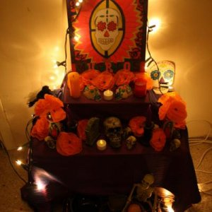 My ofrenda: A painted canvas board, homemade tissue marigolds, various candles and skulls etc, fresh water and fruit to welcome the dead and Virgin Ma
