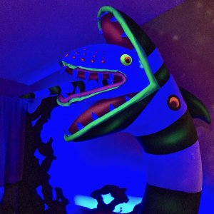 "Blacklight Painted Sandworm and ""Saturn"" cut outs behind"