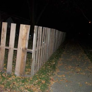 The graveyard fence going down the sidewalk.