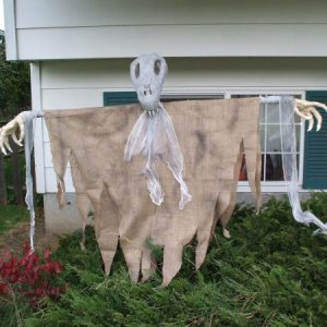 My scarecrow ghoul set up in front of the house in daylight.  It was a simple wooden 't' armature, to which I added some plastic-bag-constructed hands