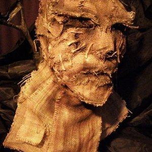 Burlap glued to a duct tape form of my own head. Added some shadows and drippy effects with an airbrush. This is wearable.