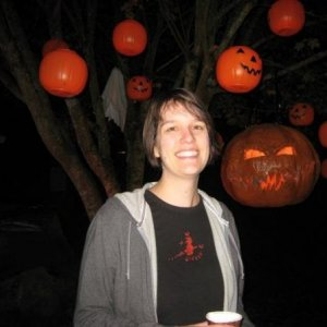 The wife (Endora421) posing next to the pumpkin tree with the big pumpkin looming.