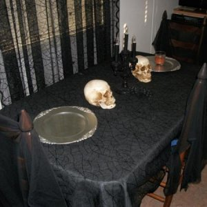 Picture 058 A marcabre table scape with Web laced cloth, Skulls, Candelabra, and gothic chargers.