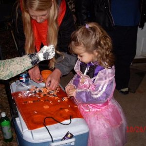 A witch helping a little Princess with decorating her Trick or treat bag