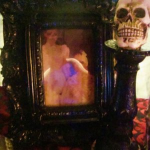 Baroque frame with haunted changing portrait, and skull candle stick.