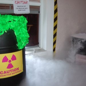 "An overflowing toxic waste barrel with dry ice caldron nearby.  Notice the sign: Caution, stop breathing when alarm sounds.  ""Toxic fog"" is"
