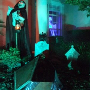 Grave digger with shovel and lantern overlooking an open coffin and corpse.  The vulture is poised to help himself.  Notice the blacklit ghost in back